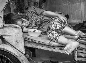 A dejected young girl lays on a worn out, unmade bed with an empty bowl in front of her