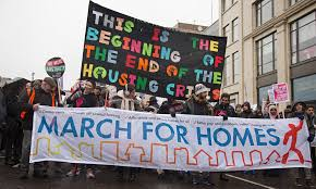 Marchers protesting gentrification with a sign that says, This is the beginning of the end of the housing crisis