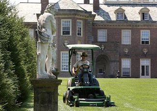 man on riding lawnmower on large Cape Cod estate