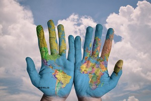 hands held together with the map of the earth brightly painted on them