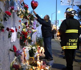 People create a memorial for victims of the Ghost Ship fire in Oakland