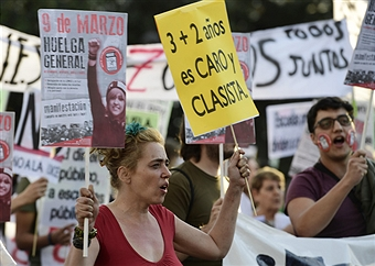 street protest with placard calling out classism in Spain's educational system
