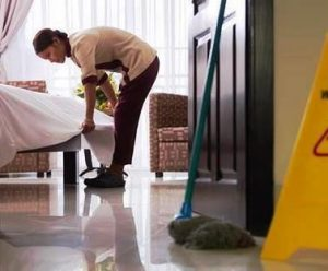 Room attendant making a bed in a hotel room