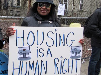 woman holding sign at protest: Housing Is a Human Right