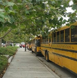 mixed-class protesters walking off of school buses that brought them to a living wage protest