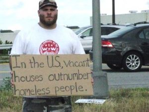 Homeless vet with sign that says, Vacant houses outnumber homeless people in the U.S.