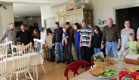lare family standing for prayer around dinner table