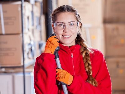Woman working in warehouse, smiling at camera